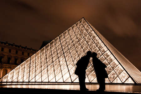 nightscene: Paris, France. January 15, 2012 - Image of the Louvre Museum Pyramid with lovers in the foreground.