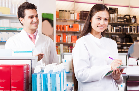 dispensary: Smiling harmacists man and harmacist woman writes in a notebookat the chemists shop of a white coat