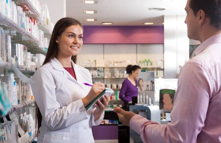 communicates: young woman in a white robe with a notebook in hand at the pharmacy communicates with the visitor