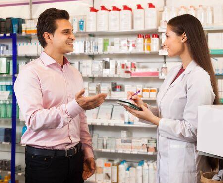 visitador medico: Mujer farmac�utico ofrece al visitante una cura en la tienda de los qu�micos Foto de archivo