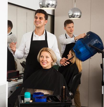 18's: Professional stylist cutting hair of elderly blonde in hairdressing salon