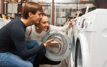 lavadora con ropa: Positive couple buying new clothes washer in supermarket