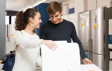 lavadora con ropa: pares de la familia feliz de comprar nueva lavadora de ropa en supermercado