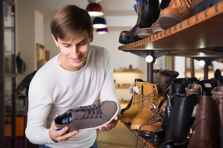 comprando zapatos: El hombre joven la compra de zapatos de verano en una tienda de zapatos