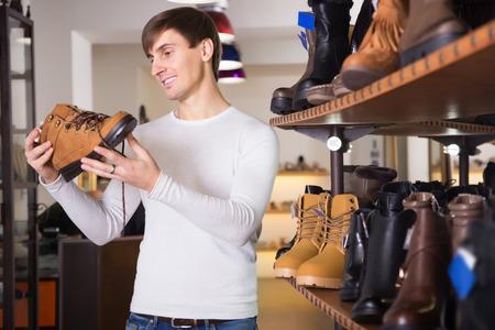 comprando zapatos: hombre feliz comprando zapatos de invierno en una tienda de zapatos