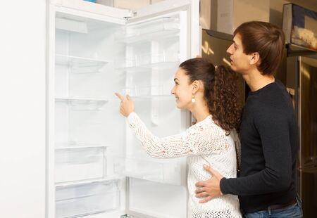 domestic appliances: Two customers looking at large fridges in domestic appliances section