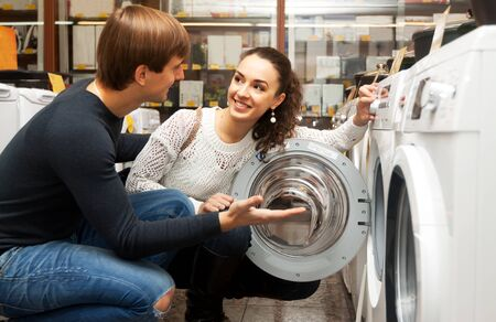 Happy european family couple buying new clothes washer in store Standard-Bild