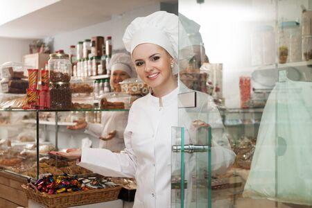 Chef con cappelli soddisfare i clienti alla porta in pasticceria