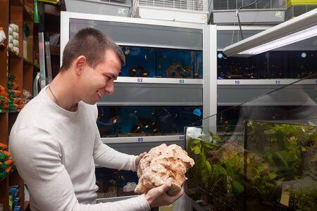petshop: young man selecting seashells for aquarium in petshop