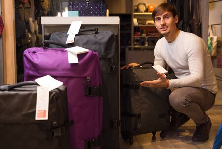 haberdashery: Young male choosing travel suitcase in haberdashery store