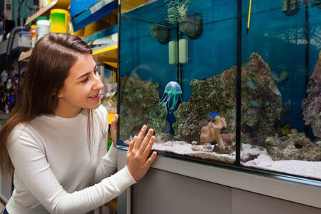 freshwater aquarium plants: Smiling young  woman watching aquarium fish in aquarium