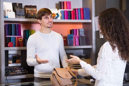 haberdashery: Young woman buying leather bag in haberdashery shop Stock Photo