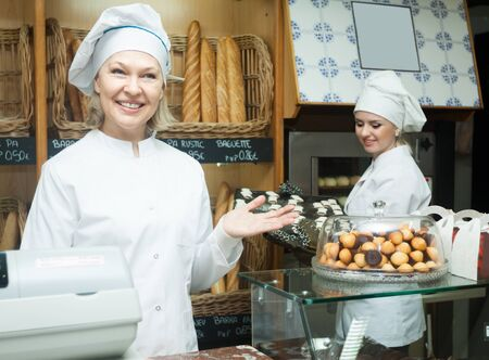25 35: Portrait of friendly blond female bakers with pastry smiling in bakery