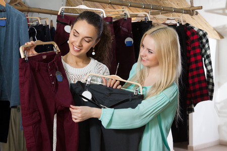 garments: Cheerful female customers looking for new garments at the store Stock Photo
