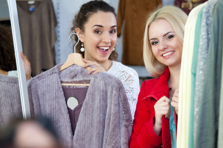 outwear: Young girlfriends shopping winter outwear at the apparel store