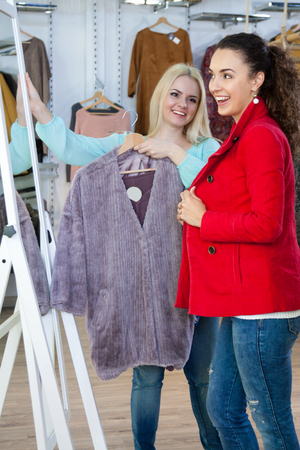 outwear: Female customers shopping winter outwear at the apparel store