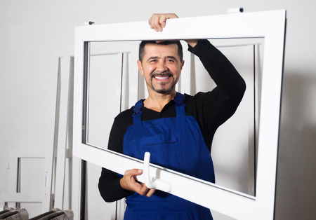 toolroom: Careful workman carrying windows frames from truck