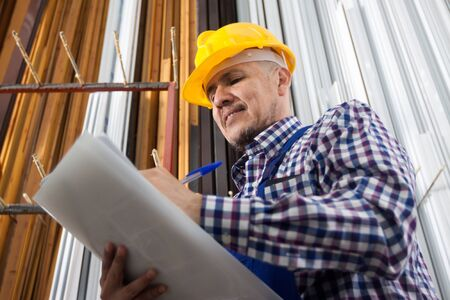 toolroom: worker in a yellow hard hat taking notes