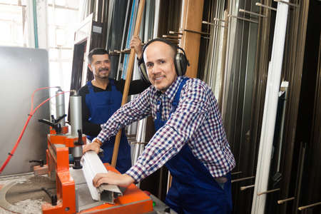 toolroom: Two smiling  professional labours working on lathe machine in PVC shop