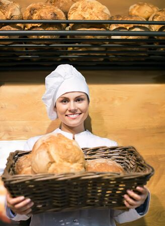 shopgirl: Happy shopgirl working in bakery with bread and different pastry Stock Photo