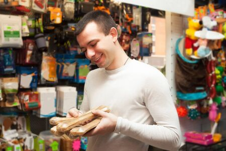 pet store: Portrait of young man with pet supplements in pet store Stock Photo