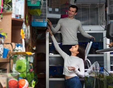 petshop: Portrait of young couple purchasing bird cage in petshop