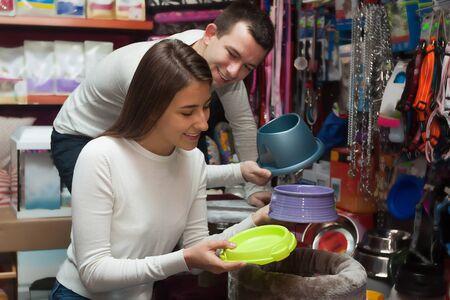 petshop: Portrait of young couple purchasing pet bowls in petshop Stock Photo