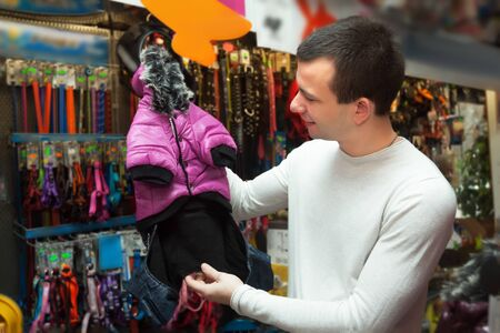 ordinary: Ordinary male customer buying clothes for pet in shop Stock Photo