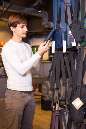 haberdashery: Young man buying new textile purse in haberdashery store