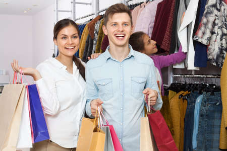 Young couple with shopping bags in their hands in a clothing store
