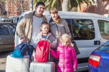 4s: Parents with two daughters with suitcases in journey