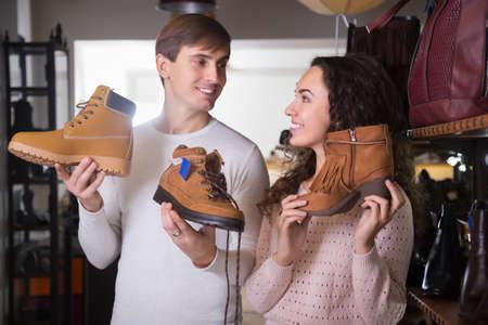 buying shoes: hombre y mujer de compra de los zapatos jovenes del invierno en una tienda de zapatos