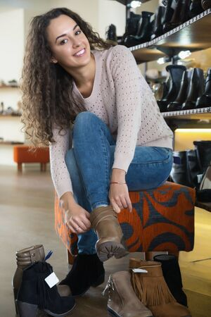 comprando zapatos: Female buying winter women shoes in a shoe store