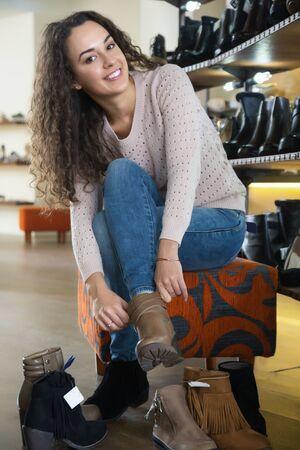 comprando zapatos: zapatos de las mujeres femeninas de invierno compra en una tienda de zapatos