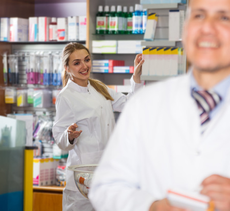 specialists: Portrait of  smiling male specialists working in modern drugstore Stock Photo