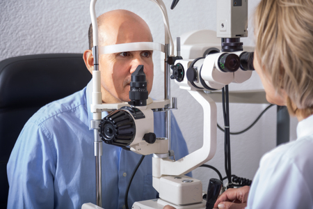 slit: Eldery female optician examinating eyesight with aid of slit lamp