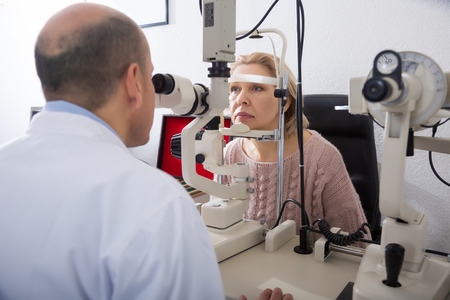 slit: Portrait of mature female who is explores eyesight with aid of slit lamp in clinic
