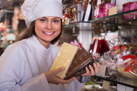 shopgirl: saleswoman selling chocolates and confectionery in cafe Stock Photo