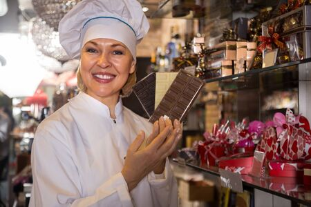 smock: mature smiling saleswoman holding chocolates in hands