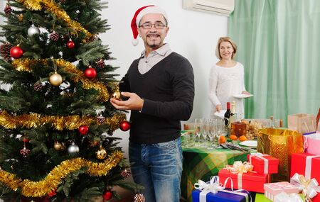 decorating christmas tree: family decorating Christmas tree and serving  festive table in home