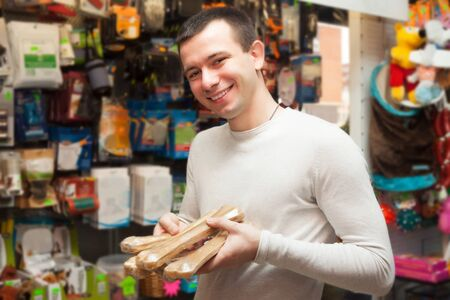 good grooming: Portrait of young man with pet supplements in store