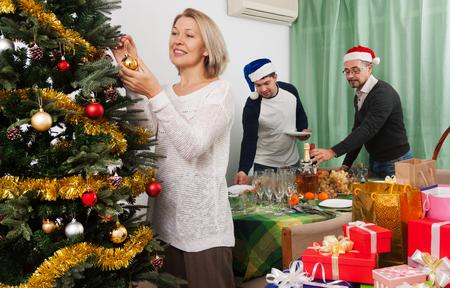 fiesta familiar: la gente que adornan el árbol de Navidad y sirviendo la mesa de fiesta en la casa
