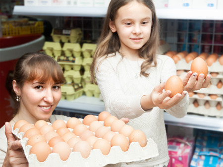 choosing selecting: Woman with curious little girl choosing selecting eggs at dairy store Stock Photo