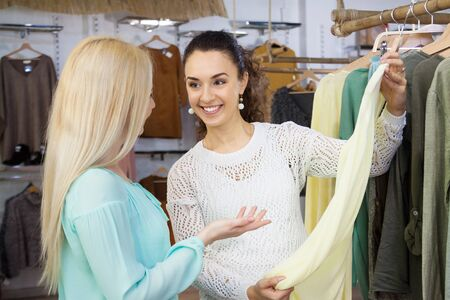 blouses: Attractive young women choosing cloths in shop