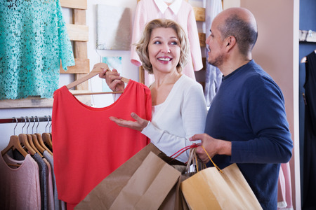 gladful: Happy adult woman selecting red dress in store Stock Photo