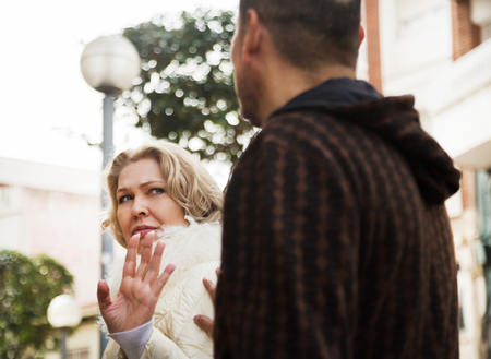 Boring male person accosting to mature female at crowded street Stock Photo