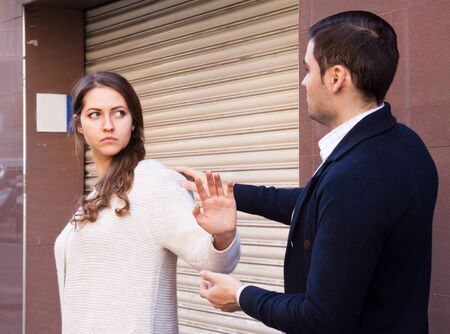 unwelcome: guy meets a girl on the street Stock Photo