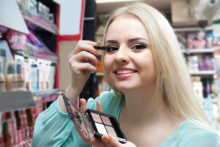 'young things': Young blonde female choosing things for make_up and smiling in a store