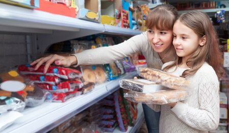 ordinary woman: Ordinary woman and little girl purchasing sweets at supermarket