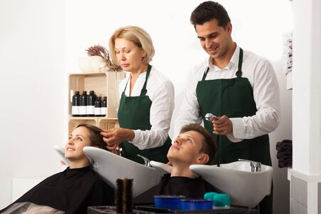 19's: Two hairdressers working with hair of clients in washing tray at the hairdresser Stock Photo